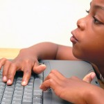 child at laptop - poor posture as chair too low