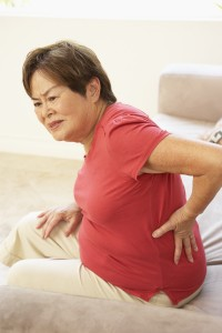 Woman with lower back pain putting hands on lower back and grimacing